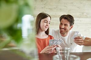 Vater und Tochter spielen Karten am Esstisch. People- und Lifestyle-Fotograf Michael Miklas - Hannover & Hamburg - fängt auch diese alltägliche Szene so ein, dass der Fokus auf dem Menschen und der positiven Stimmung liegt und nicht durch Kleinigkeiten im